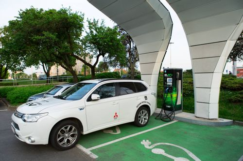 small_Mitsubishi Outlander PHEV Plug-In Hybryd at a charging station powered by solar energy.