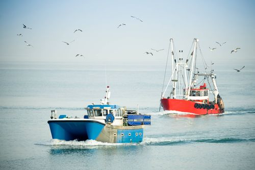small_fishing trawlers returning to port on a hazy day